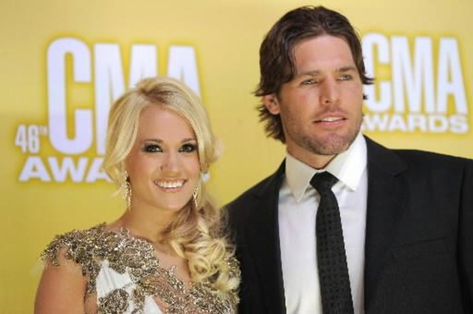 Photo -  Underwood and husband Mike Fisher arrive at the CMA Awards.
