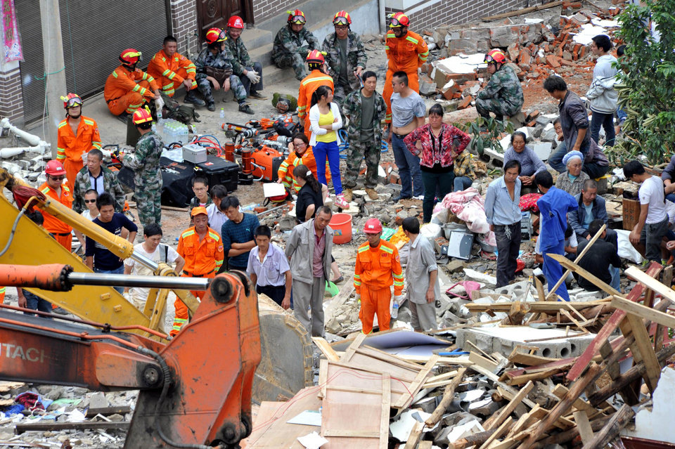 Photo - Rescuers and local residents look at destroyed houses collapsed by Sunday's earthquake in Ludian County of Zhaotong City in southwest China's Yunnan Province, Monday, Aug. 4, 2014. Rescuers dug through shattered homes Monday looking for survivors of a strong earthquake in southern China's Yunnan province that killed hundreds and injured more than a thousand people. (AP Photo/Kyodo News) JAPAN OUT