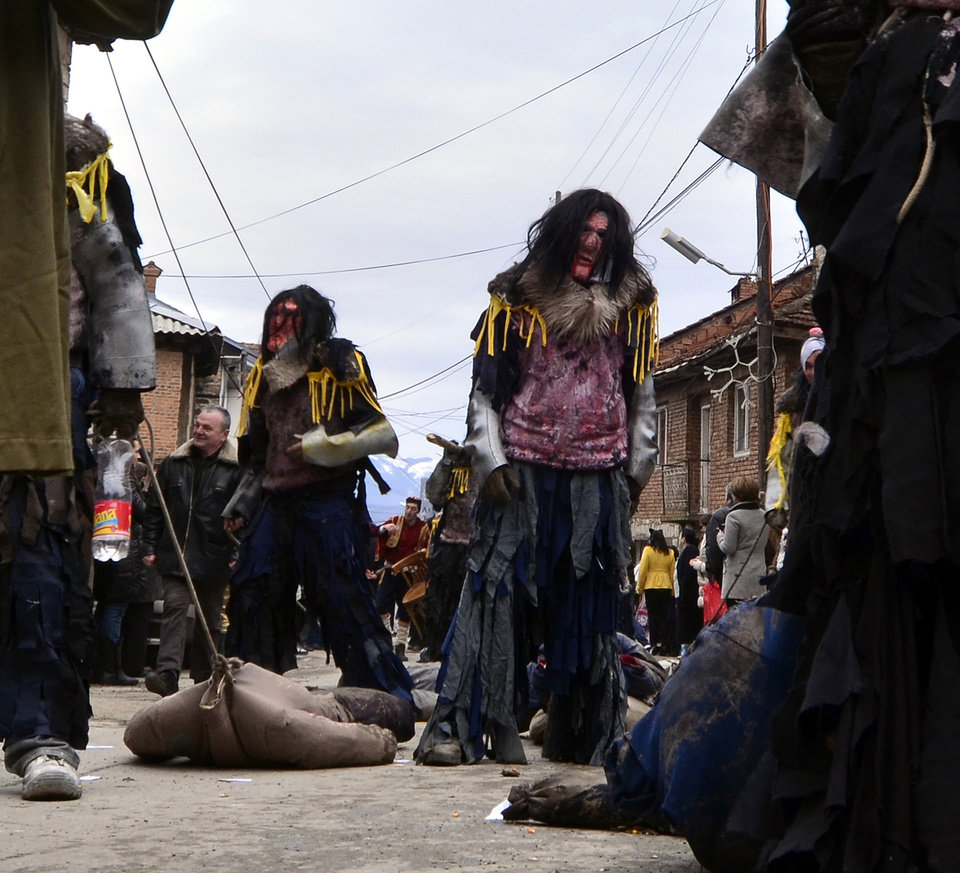 Photo - In this picture taken on Sunday, Jan. 13, 2013, villagers masked as cannibals parade during the carnival in Macedonia's southwestern village of Vevcani.  Said to date from pagan times 1,400 years ago, the Vevcani carnival, with its colorful floats and masked revelers, has grown in popularity over the last decade and attracts thousands of visitors for the celebrations on St. Vasilij Day to welcome in the New Year according to the Julian calendar. (AP Photo/Boris Grdanoski)