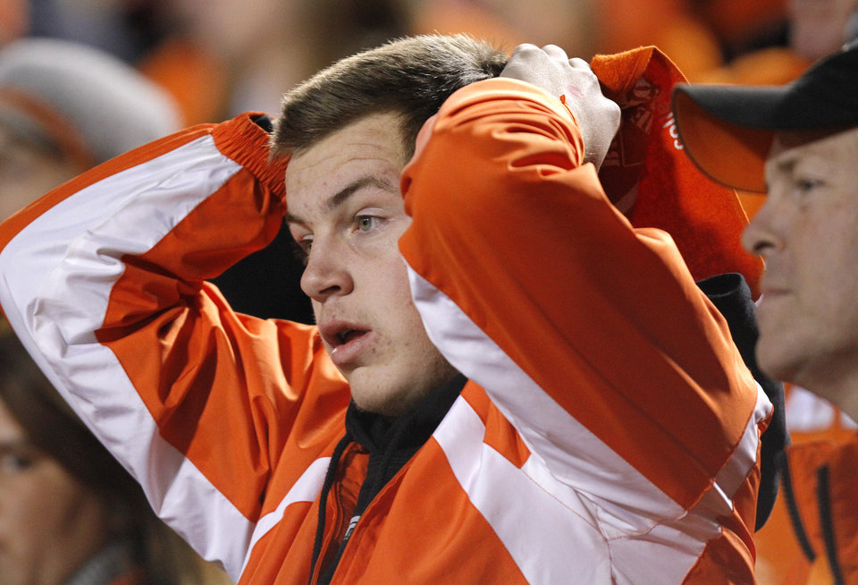 Photo - An Oklahoma State fan reacts to a Sooner touchdown in the fourth quarter during the Bedlam college football game between the University of Oklahoma Sooners (OU) and the Oklahoma State University Cowboys (OSU) at Boone Pickens Stadium in Stillwater, Okla., Saturday, Nov. 27, 2010. Photo by Chris Landsberger, The Oklahoman