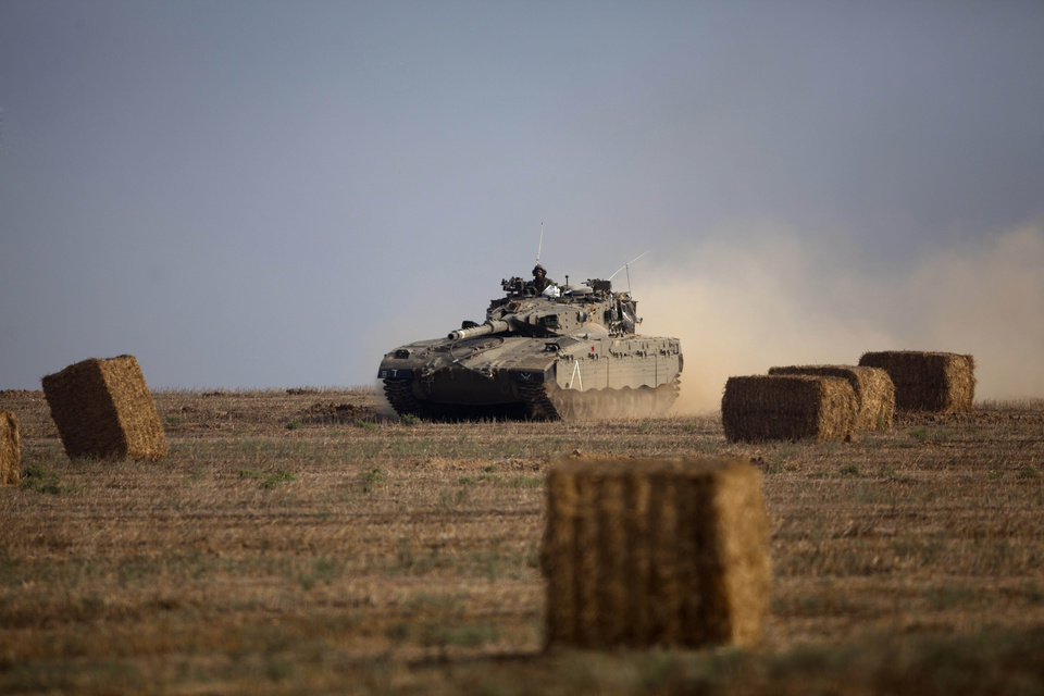 Photo - An Israeli tank runs between haystacks near the Israel and Gaza border Wednesday, July 23, 2014. Israeli troops battled Hamas militants on Wednesday near a southern Gaza Strip town, sending Palestinian residents fleeing, as the U.S. secretary of state presses ahead with top-gear efforts to end the conflict that has killed hundreds of Palestinians and tens of Israelis. (AP Photo/Dusan Vranic)
