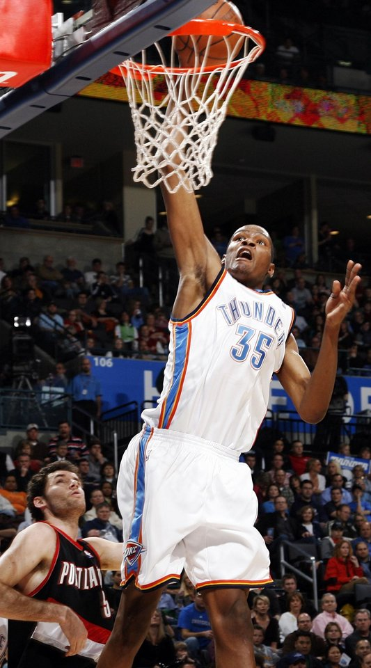 Photo - Oklahoma City's Kevin Durant (35) dunks the ball in front of Portland's Rudy Fernandez (5) in the fourth quarter during the NBA basketball game between the Oklahoma City Thunder and the Portland Trail Blazers at the Ford Center in Oklahoma City, Friday, February 6, 2009. The Thunder won, 102-93. BY NATE BILLINGS, THE OKLAHOMAN