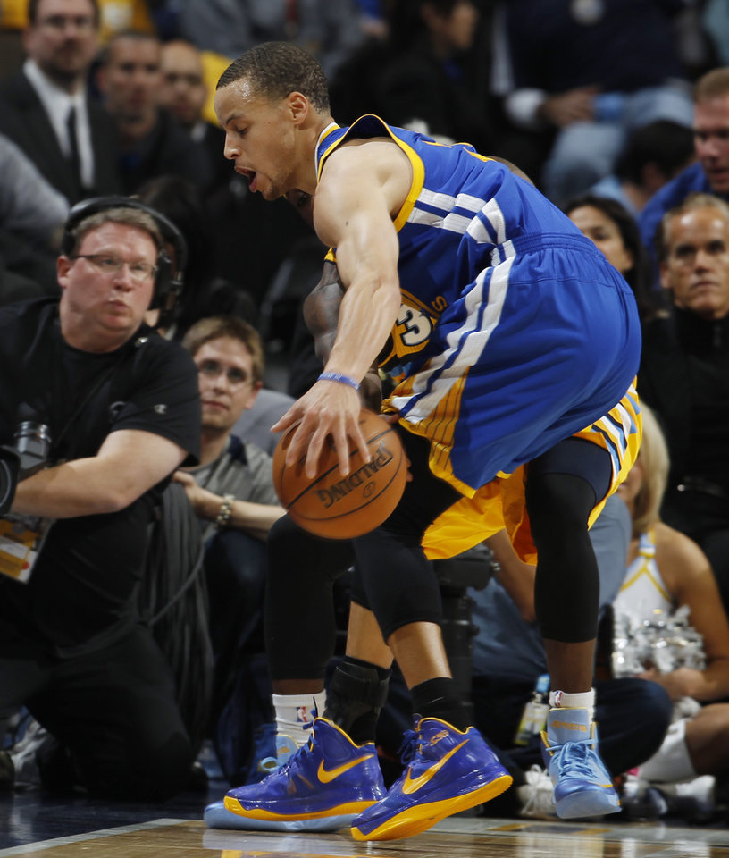 Photo - Golden State Warriors guard Stephen Curry, front, picks up a loose ball in front of Denver Nuggets guard Ty Lawson in the first quarter of Game 2 of the teams' NBA first-round playoff series in Denver on Tuesday, April 23, 2013. (AP Photo/David Zalubowski)