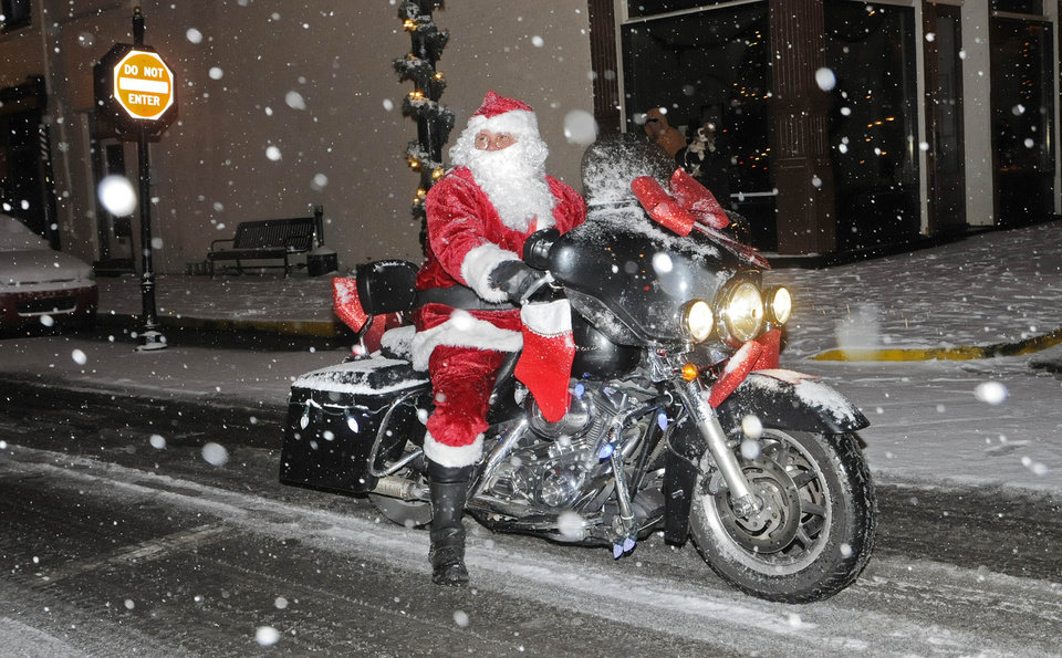 Photo - Santa rides his motorcycle along the route of the Twilight Christmas Parade Friday, Dec. 6, 2013 in Maysville, Ky during a steady snowfall.  Alan Henderson was portraying Santa Claus. (AP Photo/The Ledger Independent, Terry Prather).
