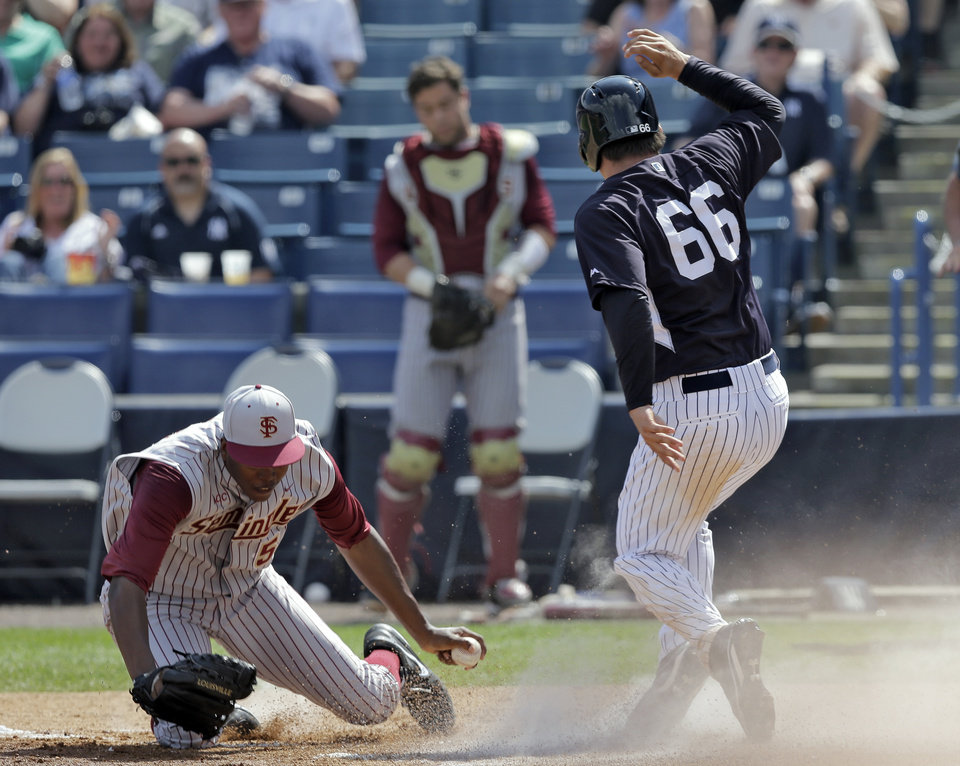 Photo - New York Yankees' John Ryan Murphy (66) scores past Florida State pitcher Brandon Johnson during the third inning of a spring training exhibition game Tuesday, Feb. 25, 2014, in Tampa, Fla. Murphy scored from third base on a pop out by teammate Gary Sanchez. (AP Photo/Chris O'Meara)