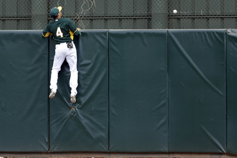 Photo - Oakland Athletics center fielder Coco Crisp watches as a home run hit by Milwaukee Brewers' Juan Francisco flies over the center field wall during the second inning of a spring training baseball game on Thursday, Feb. 27, 2014, in Scottsdale, Ariz. (AP Photo/Gregory Bull)