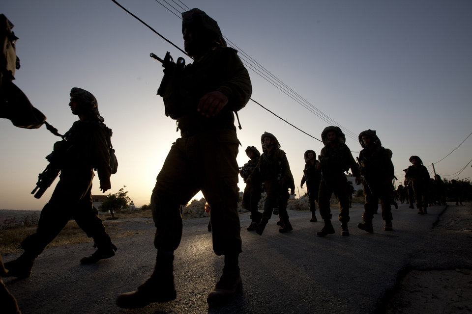 Photo - Israeli soldiers patrol during a military operation to search for three missing teenagers outside the West Bank city of Hebron, Monday, June 16, 2014. Israeli security forces searched the West Bank, looking for three missing teenagers, including an American, who they fear have been abducted by Palestinian militants. (AP Photo/Majdi Mohammed)