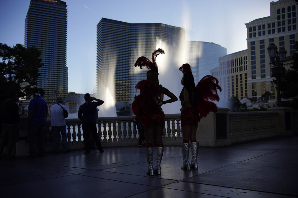 Photo -  People dressed as showgirls stand along the Las Vegas Strip, Thursday in Las Vegas. [John Locher/The Associated Press]