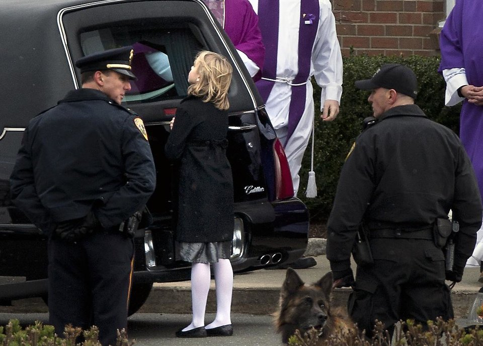 A girl looks into the hearse carrying the casket of Josephine Gay after the funeral services at St. Rose of Lima Roman Catholic Church, Saturday, Dec. 22, 2012, in Newtown. Gay, was one of 20 children and six adult victims killed in on the Dec. 14 mass shooting at Sandy Hook Elementary in Newtown.  (AP Photo/The News-Times, Cody Duty) MANDATORY CREDITCREDIT