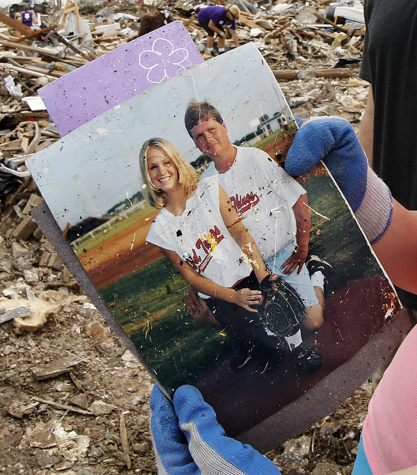 Photo - Jill Tompkins, 28, stands in the rubble of her home at 1001 SW 15, holding a picture of her with her dad, Larry Tompkins,  when she was a young softball player for the Washington Wild Things. A volunteer from Moore First Baptist Church had just handed her these photos after he recovered them from the debris. Tompkins thanked him repeatedly and smiled big, explaining to him why these pictures are of such value to her. Her dad, who was her softball coach from age five through high school, died in March. She said her dad