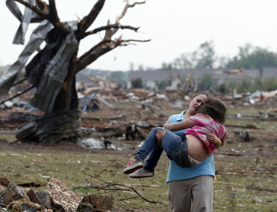 Photo - A woman carries a child through a field near the collapsed Plaza Towers Elementary School in Moore, Okla., Monday, May 20, 2013. The relationship between the woman and the child was not immediately known. A tornado as much as half a mile (.8 kilometers) wide with winds up to 200 mph (320 kph) roared through the Oklahoma City suburbs Monday, flattening entire neighborhoods, setting buildings on fire and landing a direct blow on an elementary school. (AP Photo Sue Ogrocki)