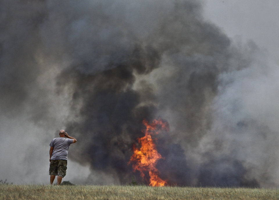 Photo - A concerned resident watches as the fire burns through a field near 63rd and Sooner Rd. on Tuesday, Aug. 30, 2011, in Oklahoma City, Okla. 