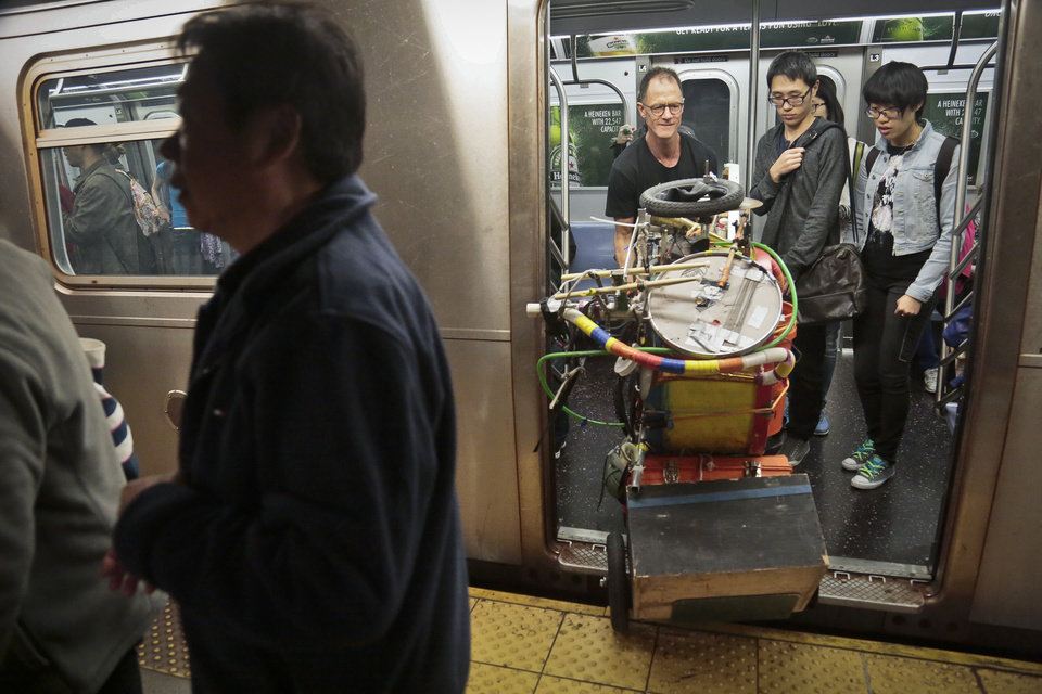 Photo - In this Wednesday, Oct. 9, 2013, photo, Jeffrey Masin, center, disembarks a subway train with his one-man band ensemble in New York. Masin, from Waterford, Conn., has performed his one-man band show he calls