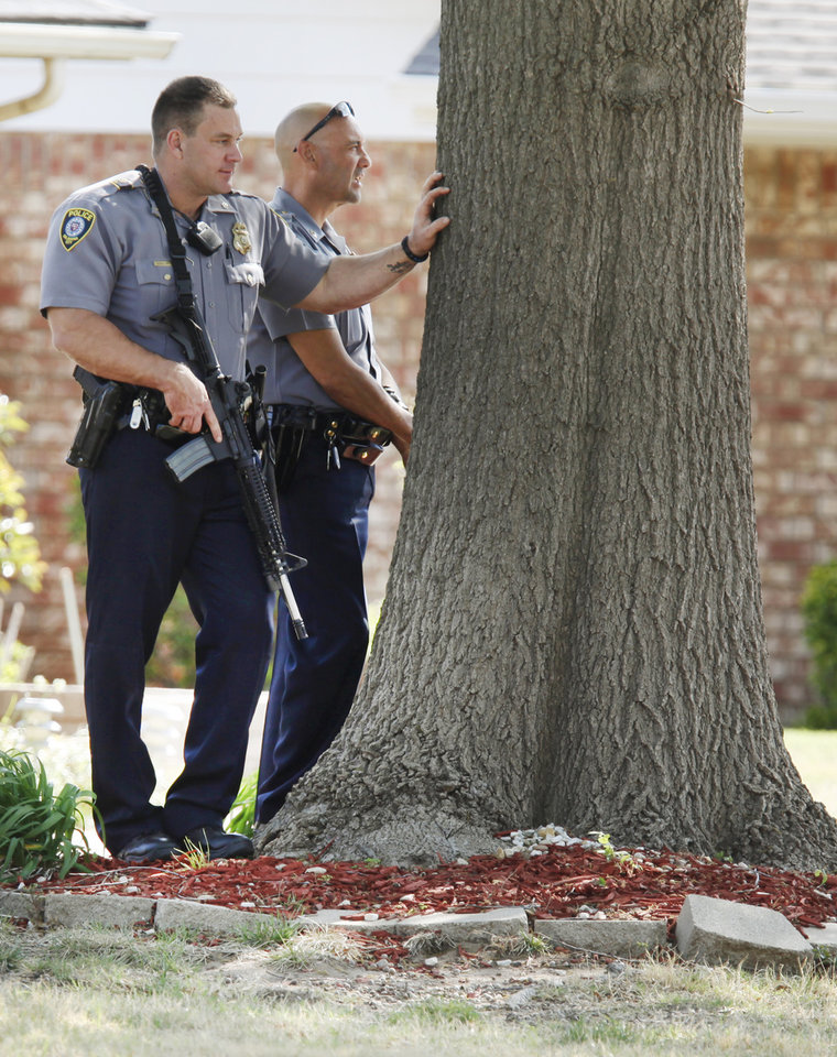 Oklahoma City police take position across the street from a home in the 4100 block of NW 60th in Oklahoma City , April 13 , 2011. Photo by Steve Gooch, The Oklahoman