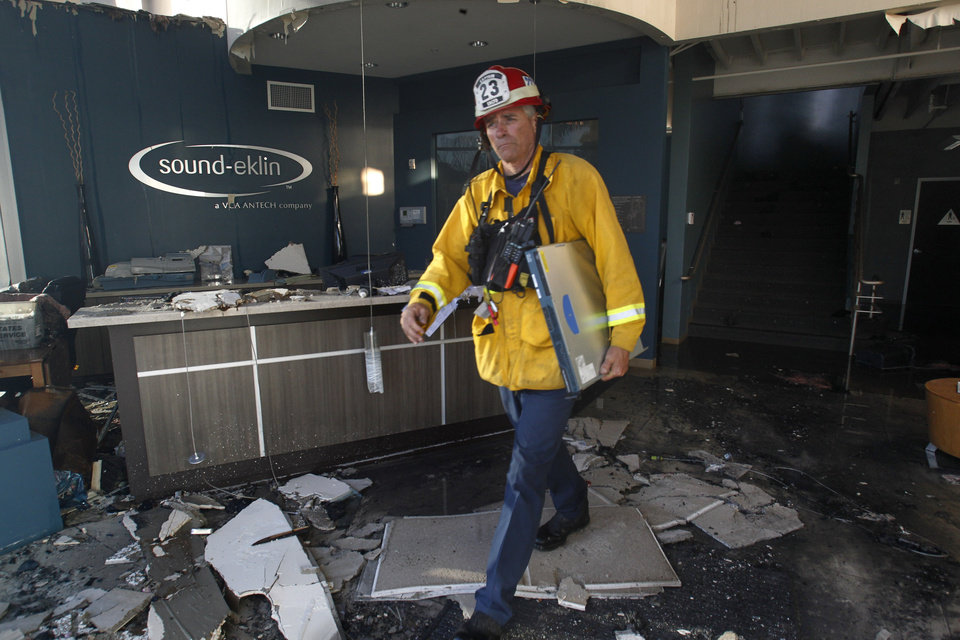 Photo - A fireman surveys the damage to the Sound-Elkin business after being hit by wildfires in Carlsbad, Calif. The fires have come during a heat wave in the drought-stricken state. (AP Photo/UT San Diego, John Gibbins)