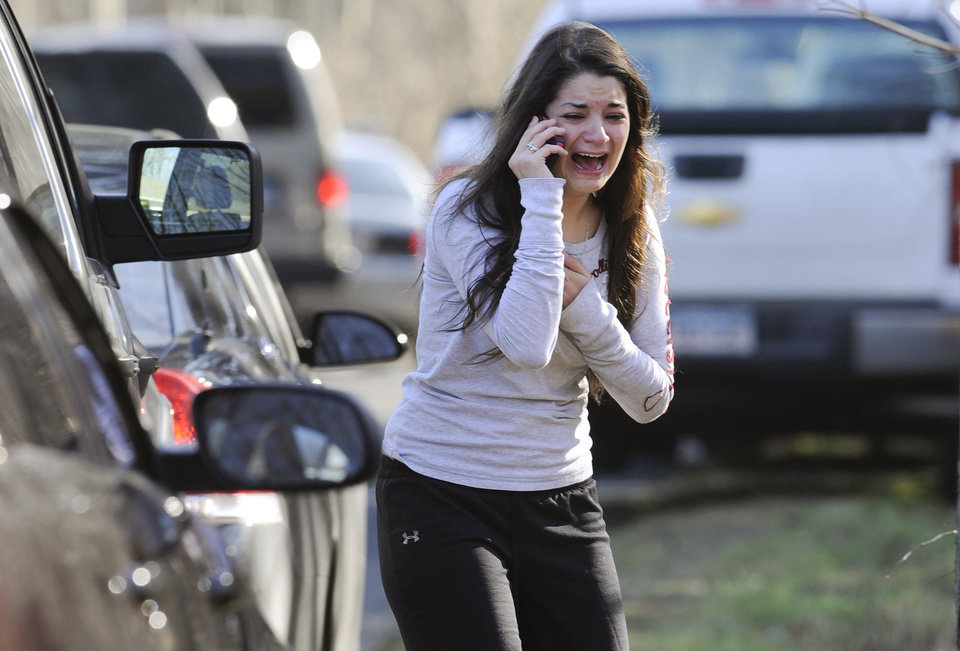Photo - Jillian Soto uses a phone to get information about her sister, Victoria Soto, a teacher at the Sandy Hook elementary school in Newtown, Conn. Friday, Dec. 14, 2012 after a gunman killed over two dozen people, including 20 children. Victoria Soto, 27, was among those killed. (AP Photo/Jessica Hill)