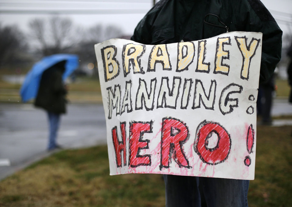 Photo -   A demonstrator holds a sign in support of Army Pfc. Bradley Manning outside of Fort Meade, Md., Tuesday, Nov. 27, 2012, where Manning is scheduled to appear for a pretrial hearing. Manning is accused of sending hundreds of thousands of classified Iraq and Afghanistan war logs and more than 250,000 diplomatic cables to the secret-spilling website WikiLeaks while he was working as an intelligence analyst in Baghdad in 2009 and 2010. (AP Photo/Patrick Semansky)