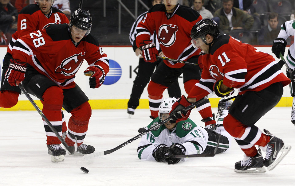 Photo - Dallas Stars left wing Ryan Garbutt falls to the ice battling for the puck with New Jersey Devils right wing Stephen Gionta (11) and New Jersey Devils defenseman Anton Volchenkov (28), of Russia, during the first period of an NHL hockey game Thursday, Jan. 9, 2014, in Newark, N.J. (AP Photo/Adam Hunger)