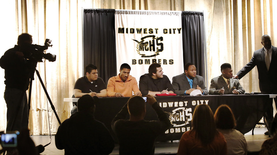 Photo - Five players from the Midwest City High School football team  signed letters of intent to play football at colleges and universities  during a ceremony  in the school's performing arts building on Wednesday, Feb. 6, 2013.   Photo by Jim Beckel, The Oklahoman
