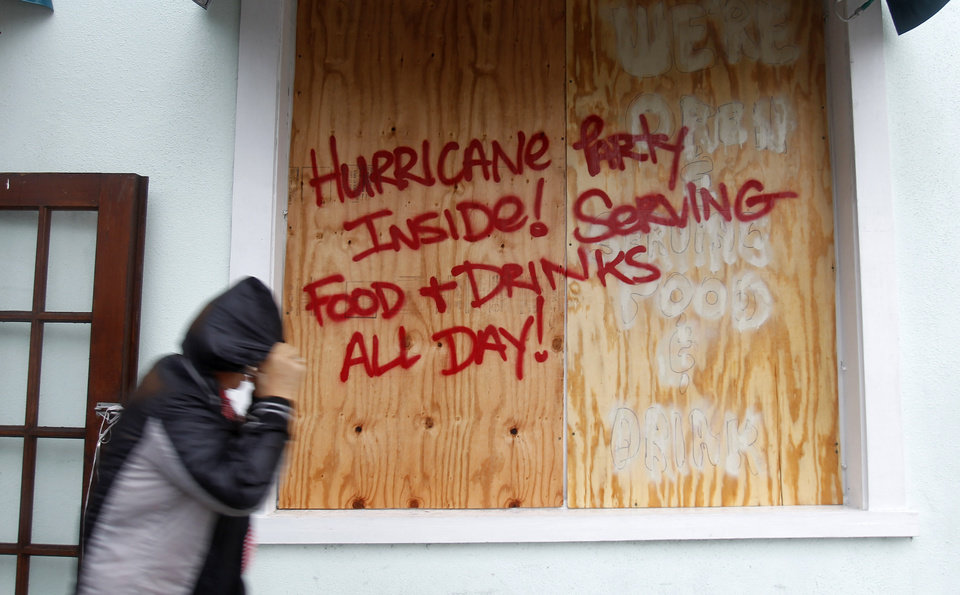 Photo - A person walks by a sign warning about Hurricane Isaac, in Key West, Fla., Sunday, Aug. 26, 2012. Isaac gained fresh muscle Sunday as it bore down on the Florida Keys, with forecasters warning it could grow into a dangerous Category 2 hurricane as it nears the northern Gulf Coast. (AP Photo/Alan Diaz) ORG XMIT: FLAD107