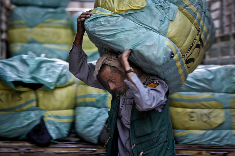 Photo - In this photo taken on Tuesday, Dec. 18, 2012, Yemeni worker, Afeef Yahya, 42, who earns 500 YR ($2.33 cents) per day, carries clothes for stock to a shop at a market in Sanaa, Yemen. According to recent government and international reports, unemployment in Yemen has risen to around 30 percent, and even 60 percent among the young. Around 54 percent of the population lives under the poverty, less than $2 per day. The unemployment rate has increased because of the political crisis and the popular uprising in 2011, forcing many factories, private enterprises, and establishments to shut down. (AP Photo/Hani Mohammed)