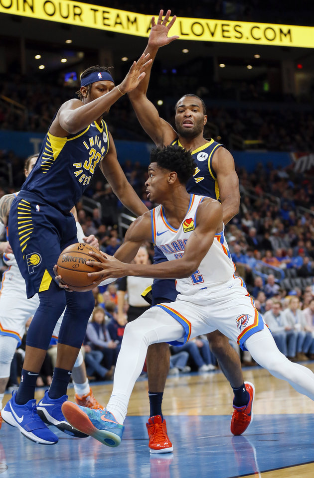 Photo - Oklahoma City's Shai Gilgeous-Alexander (2) takes the ball past Indiana's Myles Turner (33), left, and T.J. Warren (1) in the first quarter during an NBA basketball game between the Indiana Pacers and the Oklahoma City Thunder at Chesapeake Energy Arena in Oklahoma City, Wednesday, Dec. 4, 2019. [Nate Billings/The Oklahoman]