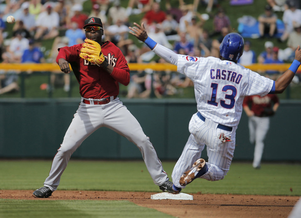 Photo - Arizona Diamondbacks' Didi Gregorius, left, forces out Chicago Cubs' Starlin Castro (13) during the first inning of a spring training baseball game on Thursday, Feb. 27, 2014, in Mesa, Ariz. (AP Photo/Matt York)