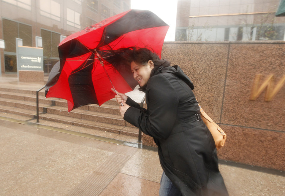 Photo - A pedestrian blocks the heavy winds with her umbrella in Los Angeles, Friday, Feb. 28, 2014.  The first wave of a powerful Pacific storm spread rain and snow early Friday through much of California, where communities endangered by a wildfire just weeks ago now faced the threat of mud and debris flows. (AP Photo/Damian Dovarganes)