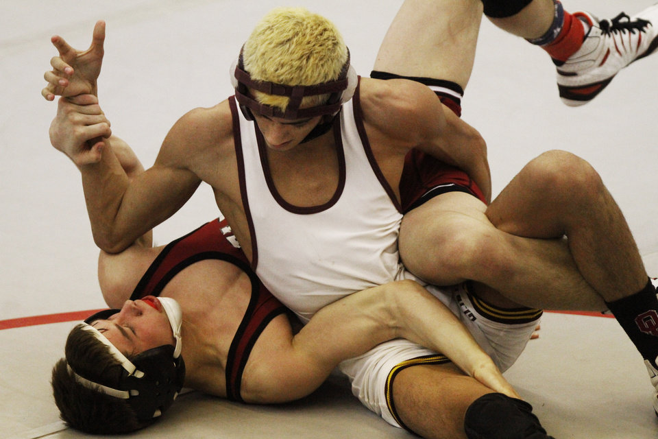 Photo - Clinton's Ryan William's (white) wrestles Tuttle's Tanner Litterell (red) in the 113 pound match at the 4A West Regional wrestling championship in Harrah on Saturday, Feb. 22, 2014. Photo by KT King, The Oklahoman