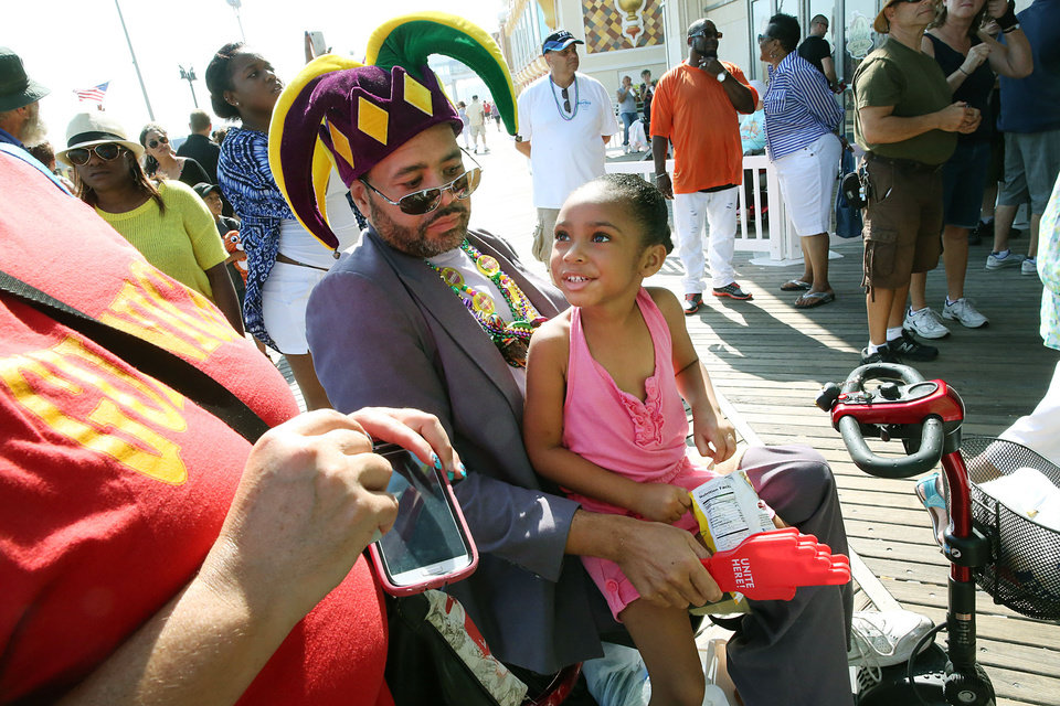 Photo - Brian Estrada of Ventnor, a former 25 year employee of the Showboat Casino, and his granddaughter, Brianna Estrada, 5, mingle with people on the Boardwalk as the Showboat Casino closed, Sunday, Aug. 31 2014.  (AP Photo/The Press of Atlantic City, Ben Fogletto)