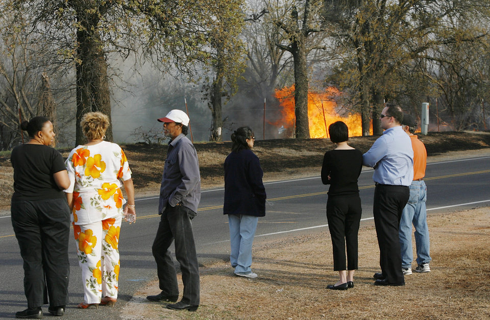 Photo - Many people were unable to access their neighborhoods after authorties issued a mandatory evacuation as wildfires marched across eastern Oklahoma County Thursday, April 9, 2009. Fire burns a wooded area as residents gather at the intersection of SE 15 and Westminster. Photo by Jim Beckel, The Oklahoman