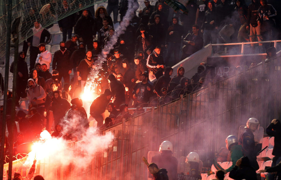 Photo - Panathinaikos fans throw flares at PAOK supporters shortly before the start of the Greek championship play-off match between their teams at Apostolos Nikolaidis stadium in Athens, Sunday, May 4, 2014. (AP Photo/InTime Sports)  GREECE OUT