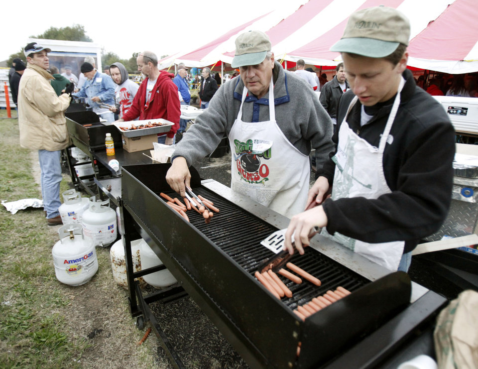 Jim Goodenow, left, and Mark Osborn cook hot dogs as LOVE OKC and Convoy of Hope distributed goods and services to metro residents at the old John Marshall High School in Oklahoma City, OK, Saturday, October 6, 2012. Services included groceries, consultations with health professionals, haircuts, family portraits, job fair, live entertainment and a free lunch for those in need. By Paul Hellstern, The Oklahoman