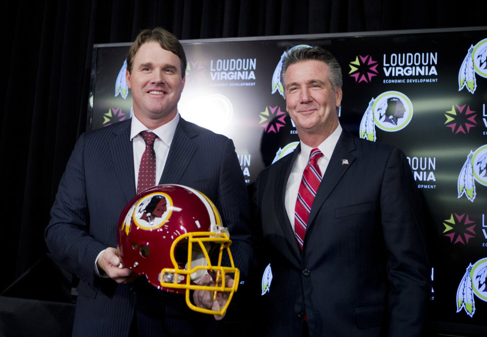 Photo - New Washington Redskins head coach Jay Gruden, holds a Redskins helmet as he poses for a picture with Executive Vice President and General Manager Bruce Allen after a news conference at the Redskins Park in Ashburn, Va., Thursday, Jan. 9, 2014.  Jay Gruden was introduced Thursday as the new Washington Redskins head coach, replacing Mike Shanahan and becoming the team's eighth head coach since Daniel Snyder purchased the franchise in 1999. (AP Photo/Manuel Balce Ceneta)