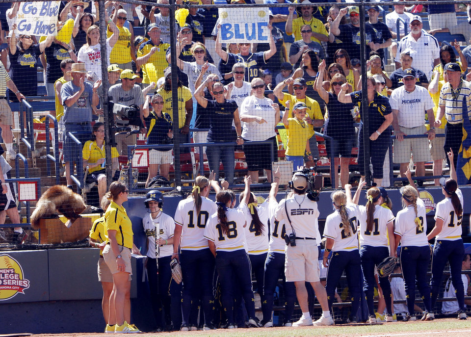 Photo - Michigan fans encourage their team between innings of the Women's College World Series elimination game versus Washington. The Washington Huskies would go on to win 4-1 on June 2, 2013. Photo by KT KING, The Oklahoman