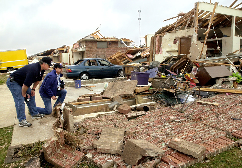 Dan Cary, left, and Mike Branick survey damage to homes in a neighborhood near SE 89 and Bryant caused by a tornado. May 9, 2003. Photo by Jim Beckel, The Oklahoman.