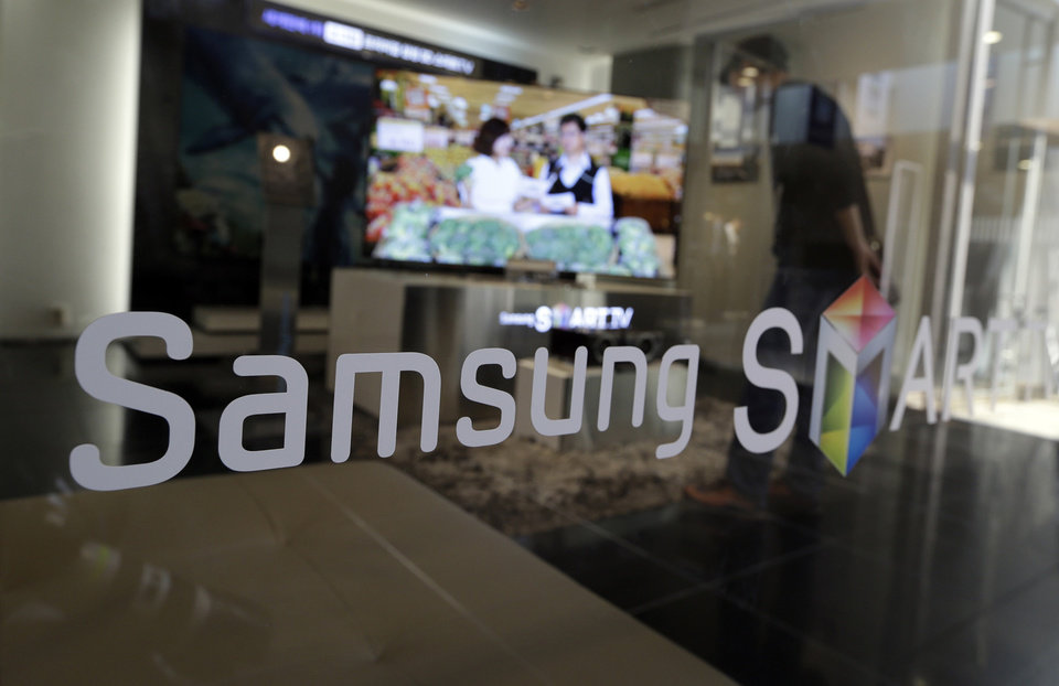 Photo -   A man watches a movie on a Samsung Electronics's product at a showroom of its headquarters in Seoul, South Korea, Friday, Oct. 5, 2012. Samsung Electronics Co. tipped all-time high quarterly operating profit, likely driven by strong sales of high-end smartphones that offset weak semiconductor orders. (AP Photo/Lee Jin-man)