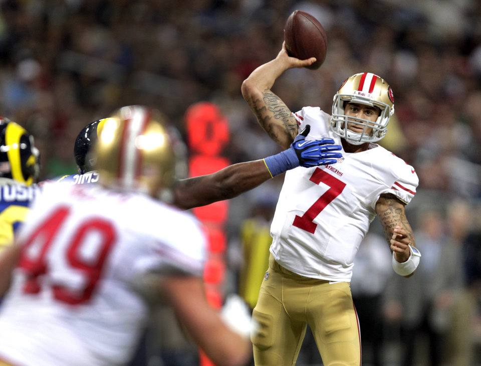 Photo - San Francisco 49ers quarterback Colin Kaepernick (7) throws to fullback Bruce Miller, left, during the first quarter of an NFL football game against the St. Louis Rams, Sunday, Dec. 2, 2012, in St. Louis. (AP Photo/Tom Gannam)