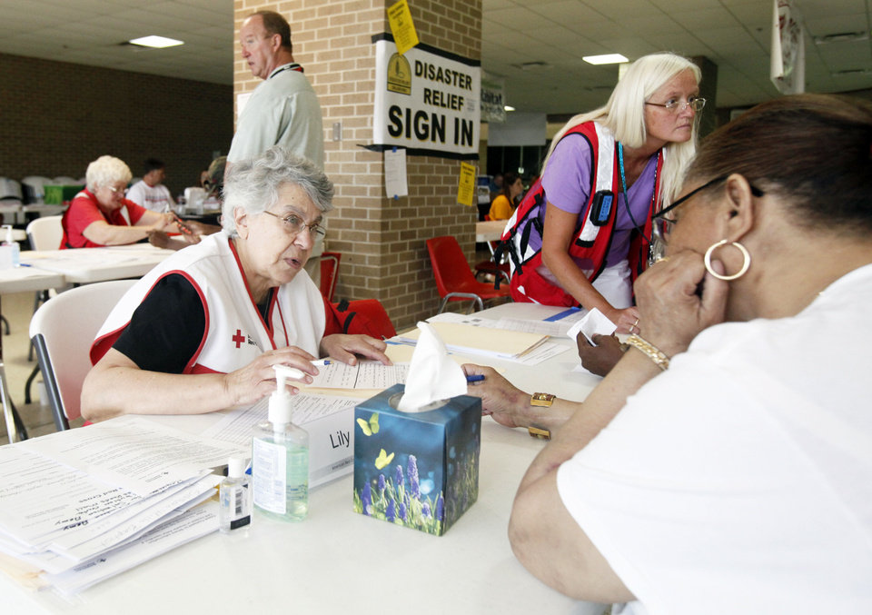 Red Cross volunteers Lily Boutros, left, of Massachusetts, and Tina Spencer, of Utah, work Wednesday with tornado victims on required relief paperwork at Westmoore High School. Photo by Aliki Dyer, The Oklahoman. <strong>Aliki Dyer</strong>