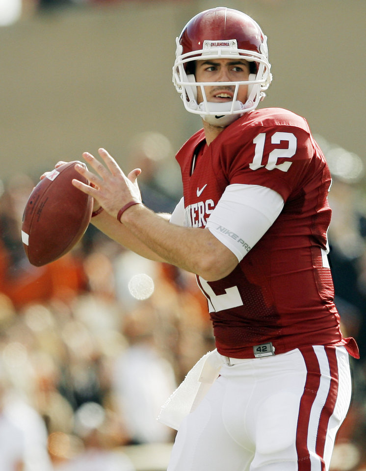 Photo - OU's Landry Jones (12) looks to pass during the first half of the Bedlam college football game between the University of Oklahoma Sooners (OU) and the Oklahoma State University Cowboys (OSU) at the Gaylord Family-Oklahoma Memorial Stadium on Saturday, Nov. 28, 2009, in Norman, Okla.