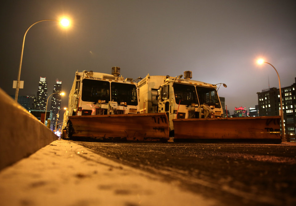 Photo - Sanitation trucks mounted with snow plows are parked on the west side of Manhattan in New York, Thursday, Jan. 2, 2014. The National Weather Service is forecasting 4 to 8 inches of snow overnight in the city. (AP Photo/Peter Morgan)
