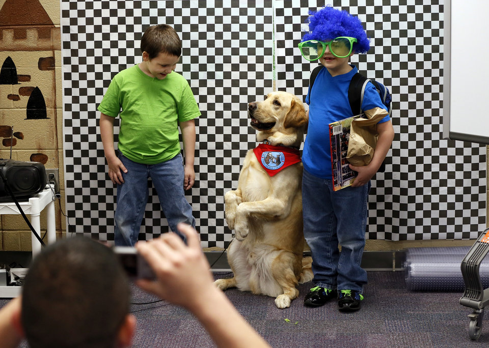 Photo - Kindergarten twin brothers Telly Keepers, left, and Tattoo Keepers, 6, pose for a photo with Jack, a therapy dog from Illinois with Therapy Dogs International, during a meet and greet with teachers and students from Plaza Towers Elementary at Eastlake Elementary School in Oklahoma City, Thursday, May 23, 2013. Seven Plaza Towers students died when a tornado destroyed the school in Moore, Okla., on Monday. Volunteers from Best Buy were taking photos of Plaza Elementary students and teachers and providing free prints. Photo by Nate Billings, The Oklahoman