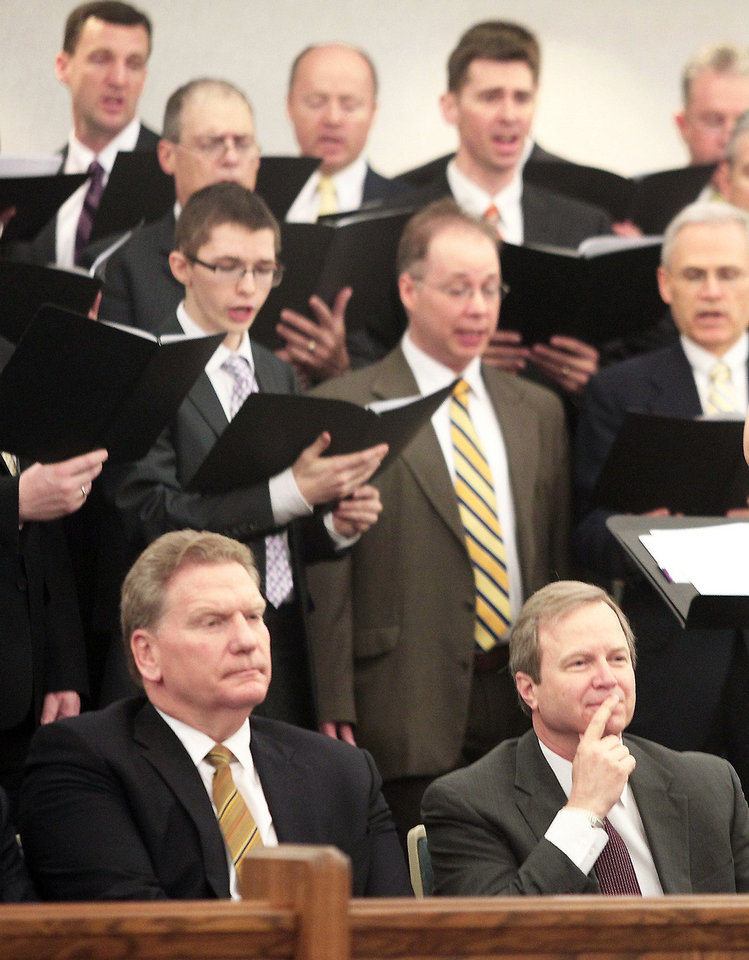 Photo - Elder Craig C. Christensen, seated at left, and Douglas L. Talley, the president of the Akron, Ohio, Stake of the Church of Jesus Christ of Latter-Day Saints, listen to the choir in April in Tallmadge, Ohio.MCT PHOTO