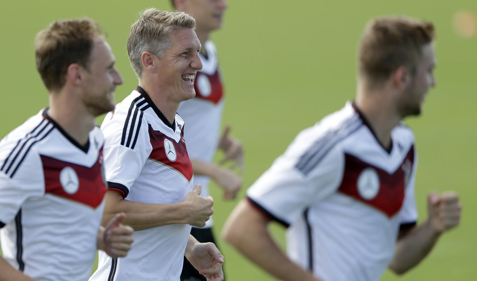Photo - German national soccer player Bastian Schweinsteiger, center, laughs during a training session in Santo Andre near Porto Seguro, Brazil, Saturday, June 14, 2014. Germany will play in group G of the 2014 soccer World Cup. (AP Photo/Matthias Schrader)