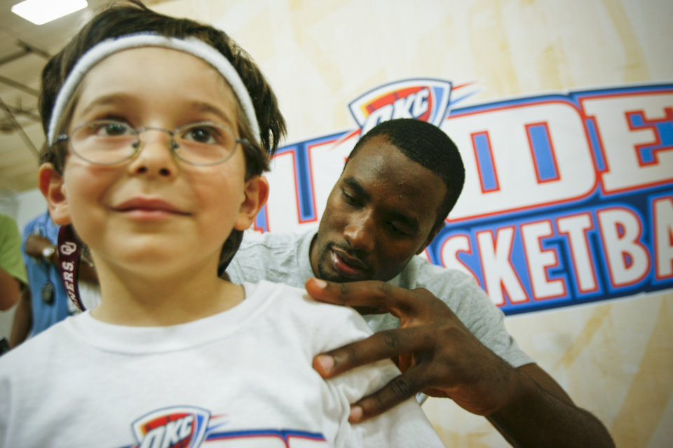 Serge Ibaka signs the shirt of Omar Kayali, 6, from Edmond at the Thunder Youth Basketball Camp at the Santa Fe Family Life Center on Tuesday, June 14, 2011. Photo by Zach Gray, The Oklahoman