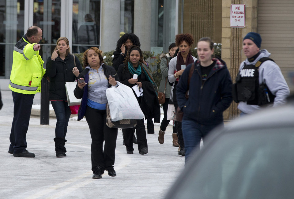 Photo - Police and law enforcement evacuate tTe Mall of Columbia after a shooting on Saturday, Jan. 25, 2014 in Columbia, Md. Police say three people died in a shooting at the mall in suburban Baltimore, including the presumed gunman. (AP Photo/ Evan Vucci)