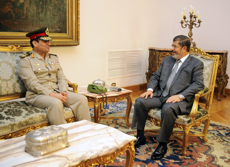 Photo - FILE - In this Monday, Aug. 13, 2012 file photo, Egyptian Minister of Defense, Lt. Gen. Abdel-Fattah el-Sissi, left, meets with Egyptian President Mohammed Morsi in Cairo, Egypt. Thousands of mourners chanting for the downfall of Egypt's president marched in funerals again Tuesday in the restive city of Port Said as the army chief warned the state could collapse if the latest political crisis drags on. (AP Photo/Egyptian Presidency, File)