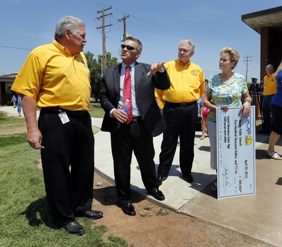Photo - Sam Porter, Baptist disaster relief director (left), Moore Public Schools Superintendent Dr. Robert Romines, Baptist General Convention of Oklahoma executive director Dr. Anthony Jordan and Becky Jackson, Principal at Central Elementary talk next to the proposed shelter site as they announce a gift from the Baptist General Convention of $500,000 to Moore Public Schools for construction of a storm shelter on Wednesday, April 23, 2014 in Moore, Okla.  Photo by Steve Sisney, The Oklahoman
