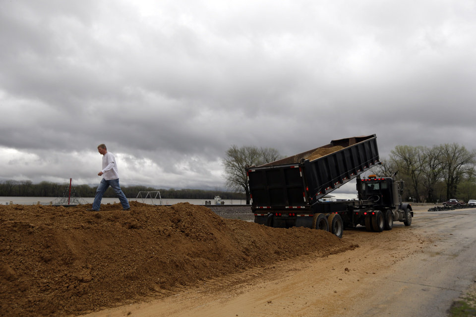 Photo - A man walks along a temporary levee being quickly constructed in hopes of holding back the rising Mississippi River Thursday, April 18, 2013, in Clarksville, Mo. Middle America was overwhelmed by weather Thursday, with snow in the north, tornadoes in the Plains, and torrential rains that caused floods and transportation woes. (AP Photo/Jeff Roberson)