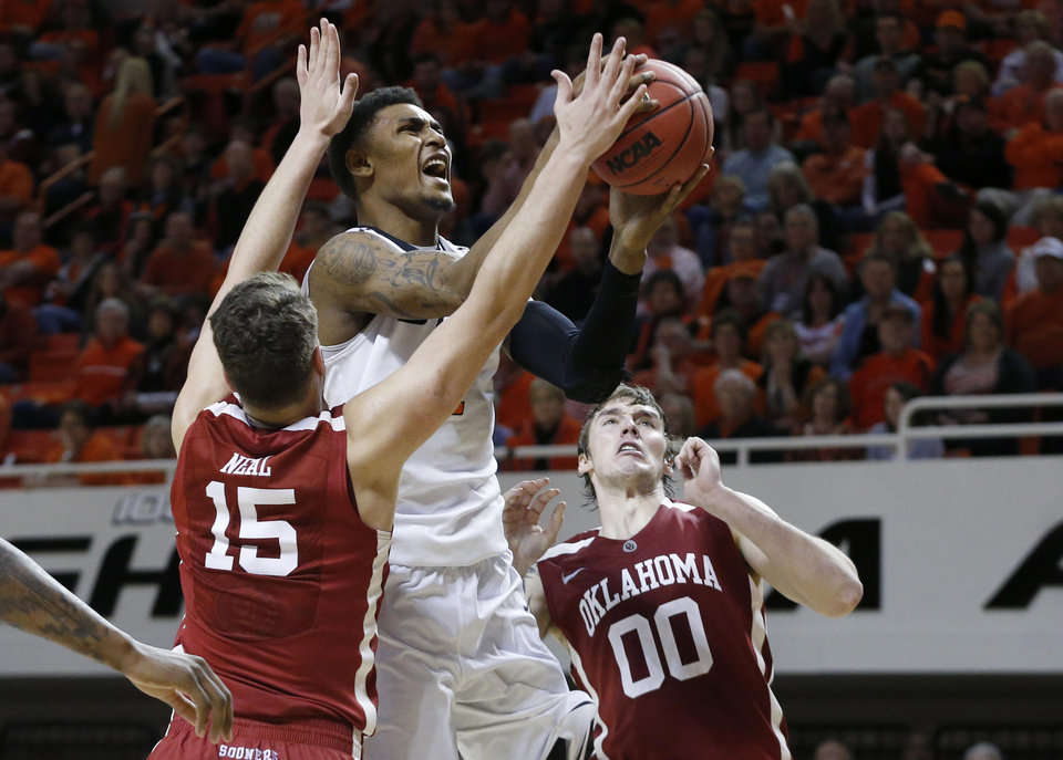 Photo - Oklahoma State wing Le'Bryan Nash (2) shoots between Oklahoma forward Tyler Neal (15) forward Ryan Spangler (00) during the second half of an NCAA college basketball game in Stillwater, Okla., Saturday, Feb. 15, 2014. Oklahoma won 77-74. (AP Photo/Sue Ogrocki)